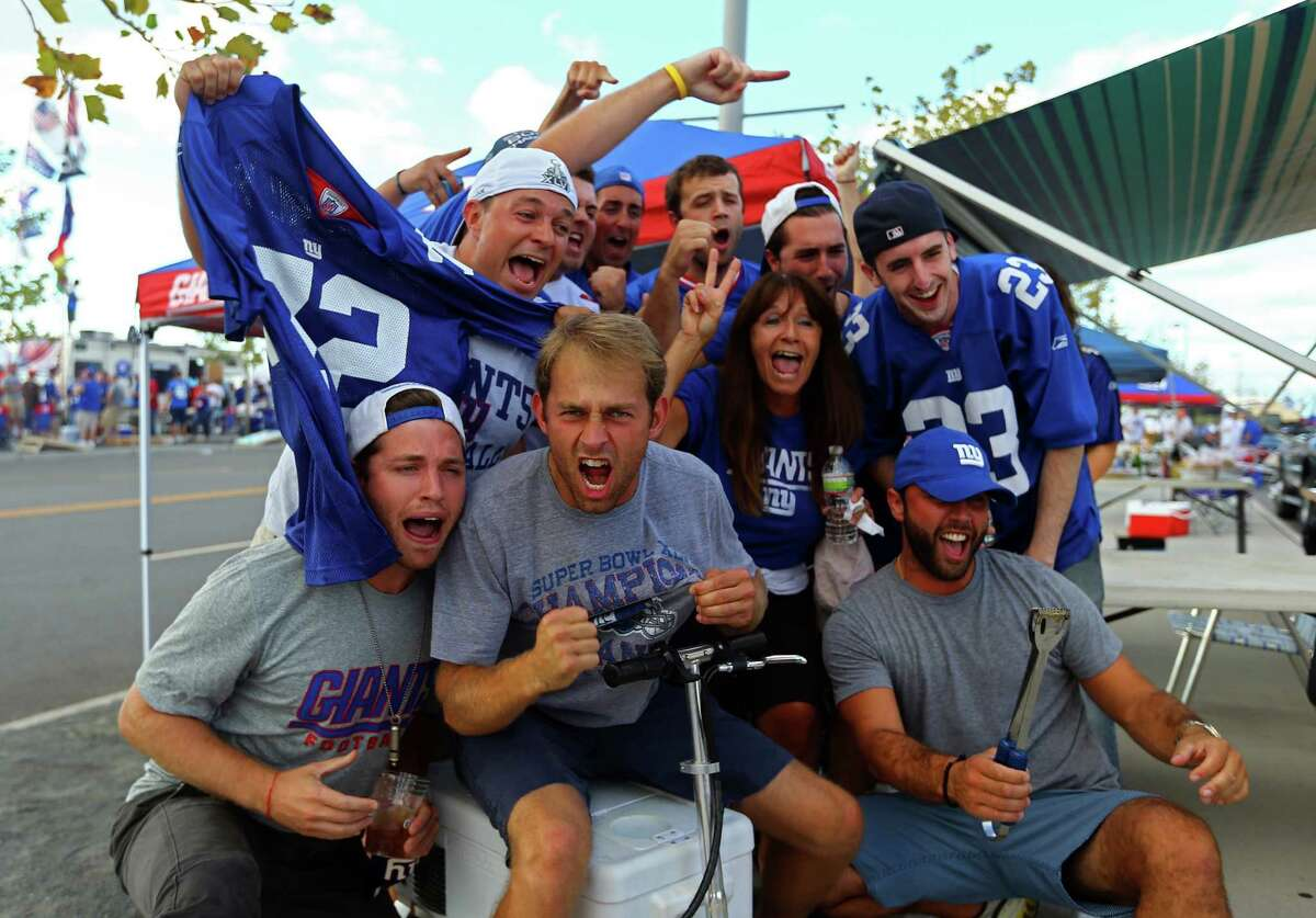 EAST RUTHERFORD, NJ - SEPTEMBER 05: Fans of the New York Giants pose for a photo outside of MetLife Stadium prior to the 2012 NFL season opener between the New York Giants and the Dallas Cowboys on September 5, 2012 in East Rutherford, New Jersey.
