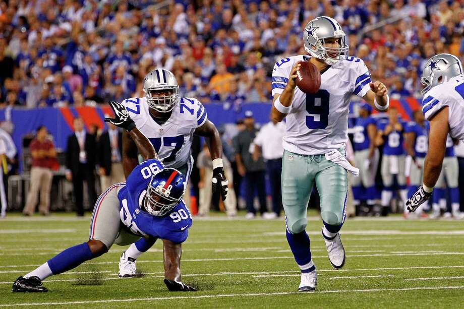 EAST RUTHERFORD, NJ - SEPTEMBER 05:  Quarterback Tony Romo #9 of the Dallas Cowboys runs with the ball on his way to throwing a touchdown to wide receiver Kevin Ogletree #85 in the second quarter as he his chased by defensive end Jason Pierre-Paul #90 of the New York Giants during the 2012 NFL season opener at MetLife Stadium on September 5, 2012 in East Rutherford, New Jersey. Photo: Jeff Zelevansky, Getty Images / 2012 Getty Images