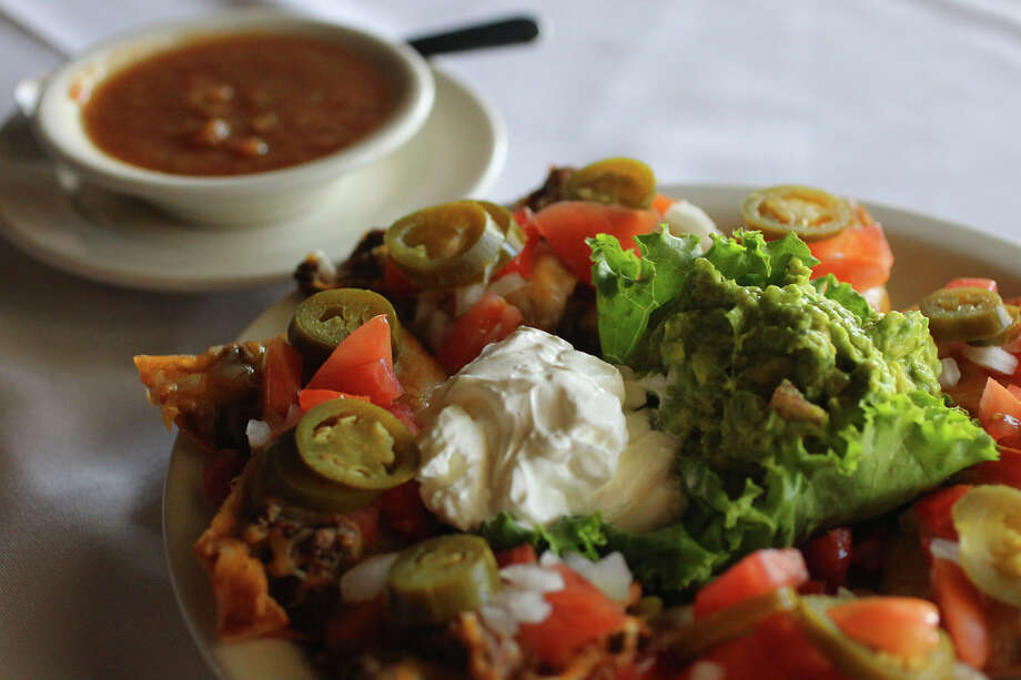 "The ""Cinco Nachos"" at Raffles Restaurant & Bar come with beef, beans, guacamole, cheese, tomato, onion and jalapenos. Photo: John Davenport, San Antonio Express-News / San Antonio Express-News"