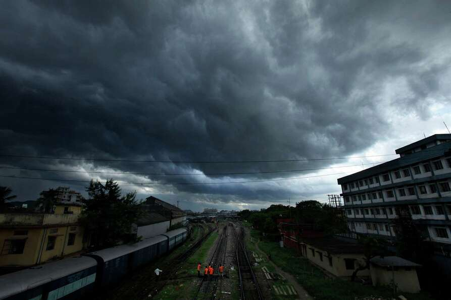 Monsoon clouds hover over a train track in Gauhati, India, Thursday, Sept. 6, 2012. The monsoon rain