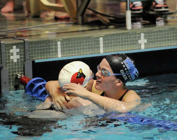 Caroline Orem, right, of Darien High School hugs Greenwich swimmer Lauren Church after the 100 yard backstroke event which Church won during the girls CIAC State Open Swimming Championships at Yale University, New Haven, Saturday, Nov. 19, 2011. Photo: Bob Luckey / Greenwich Time