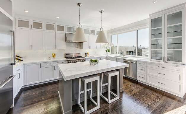 The updated kitchen has modern appliances, sleek marble finishes. Photo: Dan Friedman