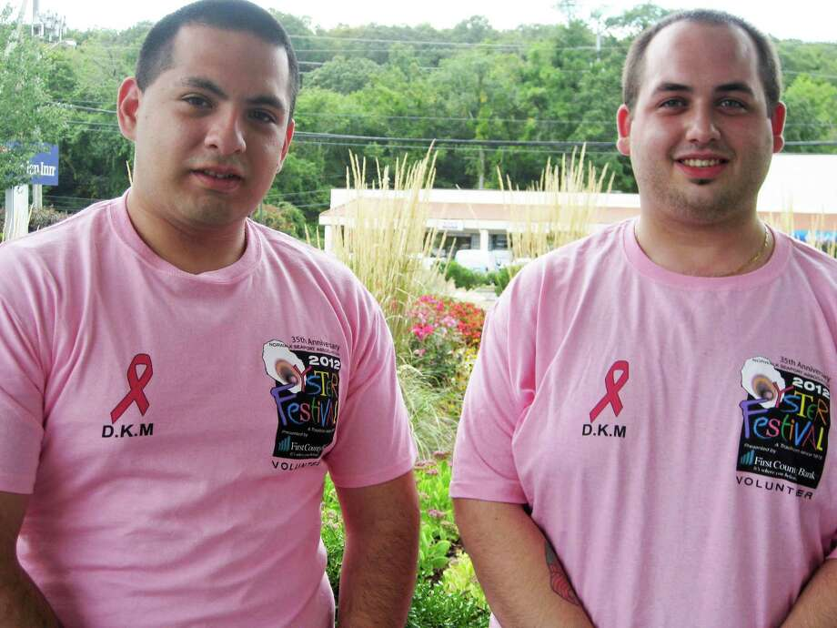 Norwalk Oyster Festival volunteers and Hilton Garden Inn Norwalk employees Stuart Burga and Chris Volpe wear the pink t-shirts that will promote breast cancer awareness at this year's event, slated for Sept. 7-9 at Veteran's Park in Norwalk. Photo: Contributed Photo