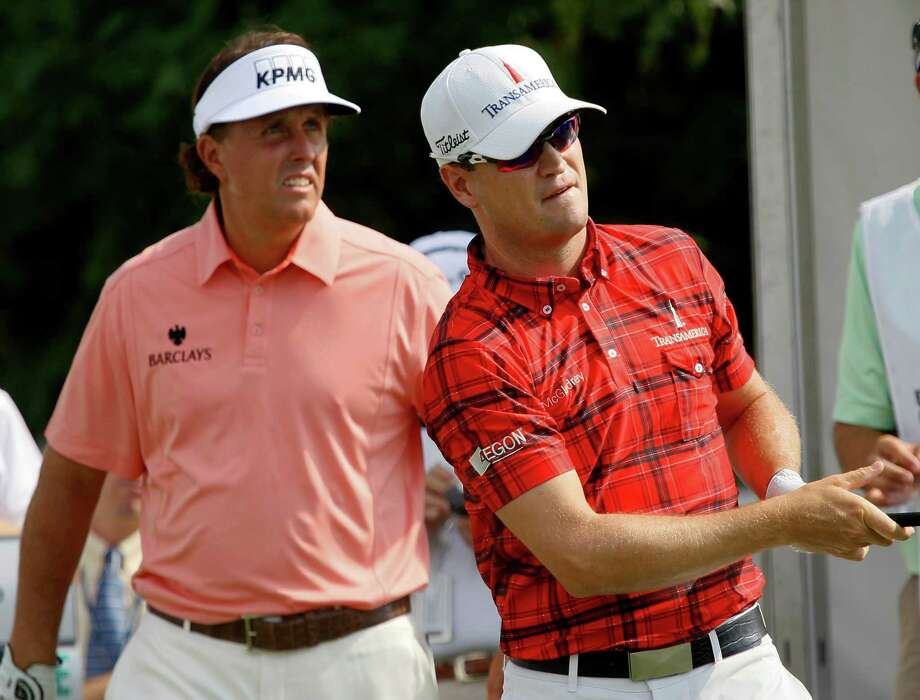 Zach Johnson, right, watches his tee shot on the 10th hole as  Phil Mickelson walks behind during the first round of the BMW Championship PGA golf tournament at Crooked Stick Golf Club in Carmel, Ind., Thursday, Sept. 6, 2012. (AP Photo/Charles Rex Arbogast) Photo: Charles Rex Arbogast, Associated Press / AP