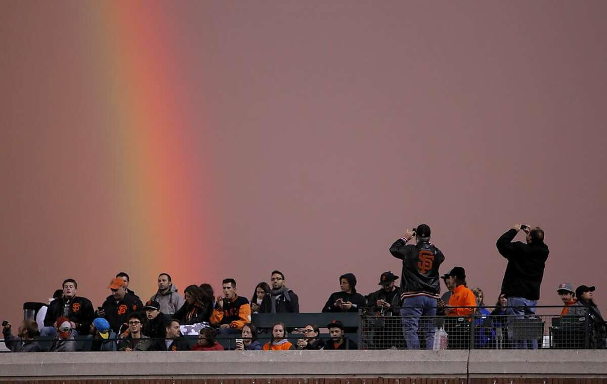 Giants fans turn to photograph double rainbow that delighted spectators as the San Francisco Giants played the Arizona Diamondbacks at AT&T Park in San Francisco, Calif., on Wednesday, September 5, 2012.