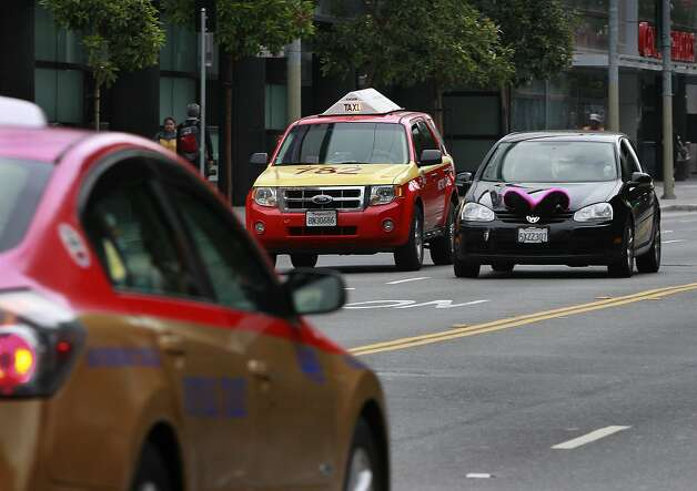 Driving a Volkswagen with its pink Lyft mustache flipped up, Shelby Stone shares the road with taxicabs, a more traditional form of getting a ride, in San Francisco last month. Photo: Paul Chinn, The Chronicle