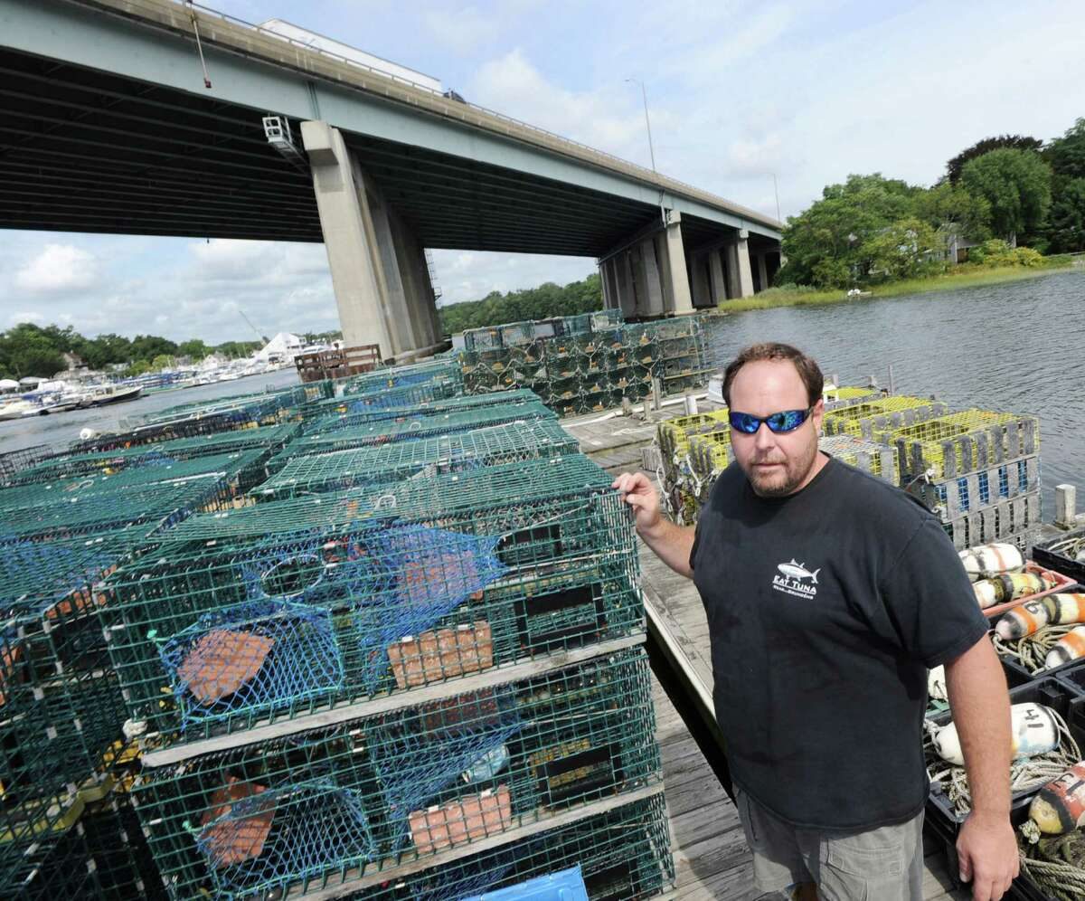 Lobsterman Gus Bertolf Jr. of Cos Cob stands on his floating dock among lobster traps in Cos Cob Harbor, Thursday, Sept. 6, 2012. Lobster catches have gone down in Long Island Sound and Bertolf blames pollution for the decline in population. In the background is the Michael L. Morano Bridge, more commonly known as the Interstate 95 Mianus River Bridge.