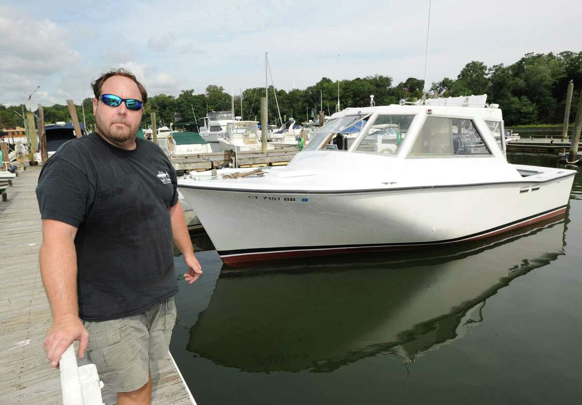 Lobsterman Gus Bertolf Jr. of Cos Cob stands dockside with his 30-foot boat, Island Girl, docked in Cos Cob Harbor, Thursday, Sept. 6, 2012. Lobster catches have gone down in Long Island Sound and Bertolf blames pollution for the decline in population.