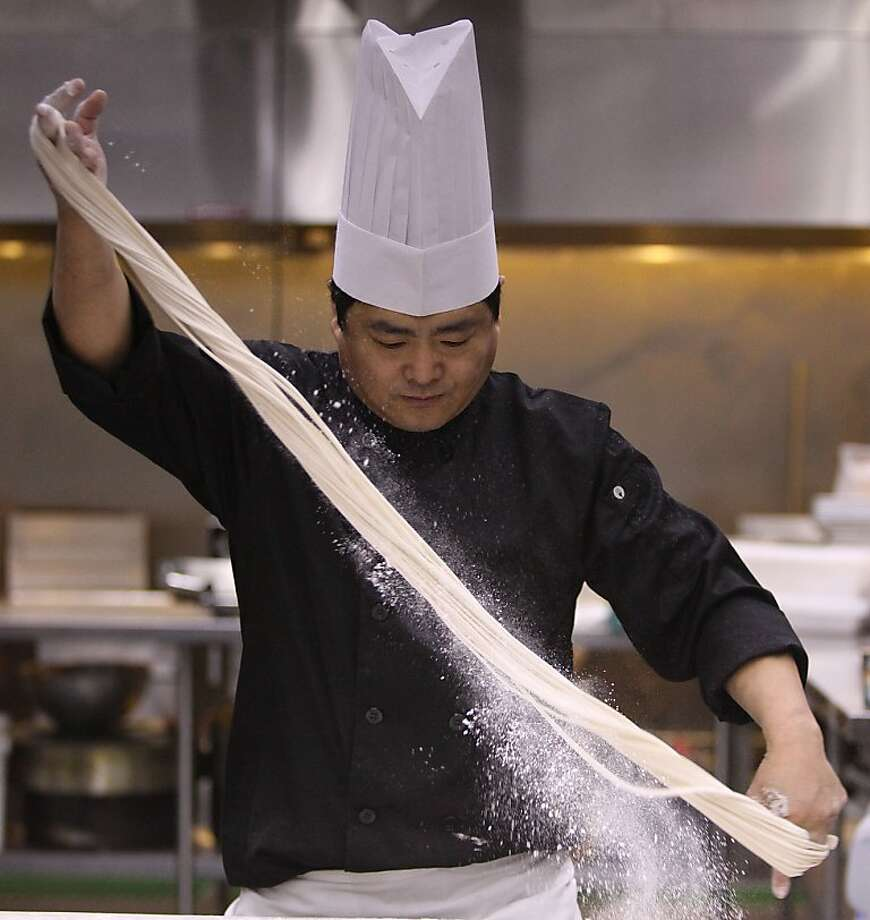 Martin Yan's master chef de cuisine Tony Wu shows how to pull noodles, lots of them, very quickly. Photo: Liz Hafalia, The Chronicle
