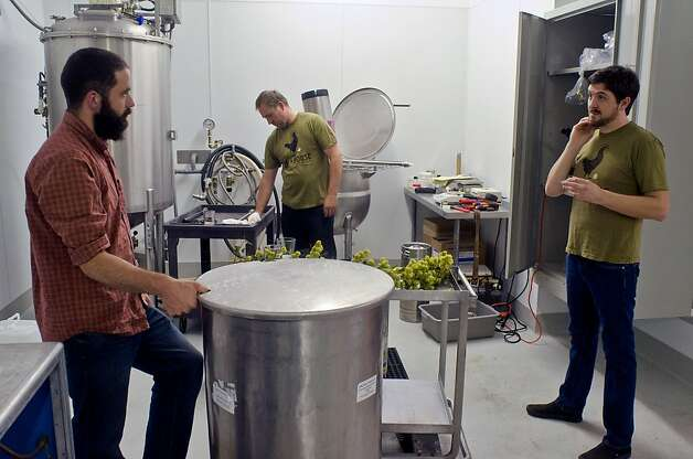 HenHouse Brewing Company's Collin McDonnell (left), Scott Goyne and Shane Goepel coordinate schedules for brewing their next batch of craft beer in Petaluma, California on August 31, 2012. Photo: Alvin Jornada, Special To The Chronicle