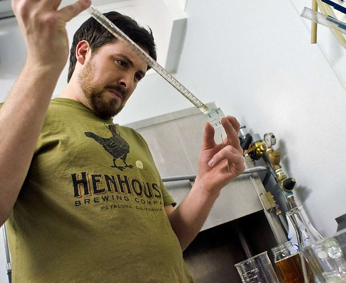 Shane Goepel places droplets of HenHouse Brewing Company's Golden Ale on a microscope slide to check yeast content during the brewing process.