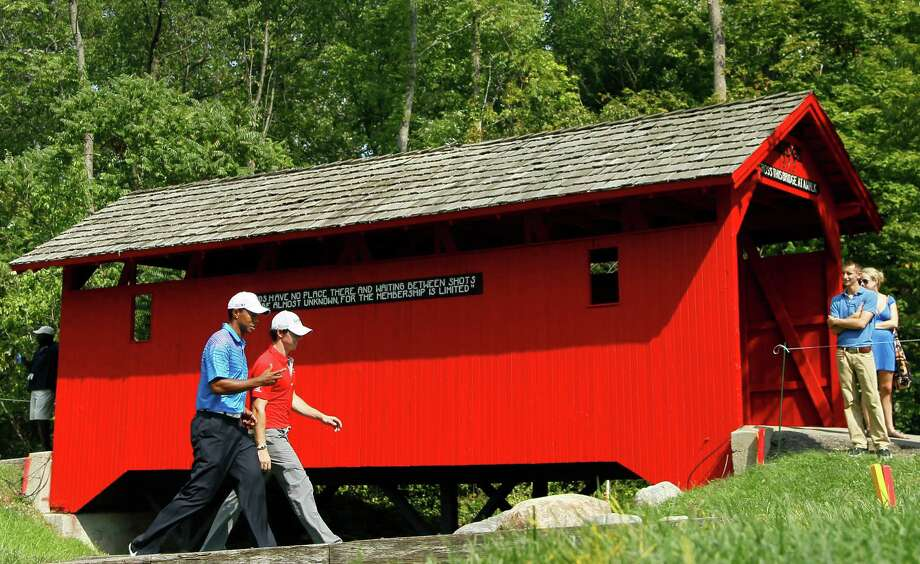 Tiger Woods, left, and Rory McIlroy, of Northern Ireland, walk past the covered bridge at the sixth hole during the first round of the BMW Championship PGA golf tournament at Crooked Stick Golf Club in Carmel, Ind., Thursday, Sept. 6, 2012. (AP Photo/Charles Rex Arbogast) Photo: Charles Rex Arbogast, Associated Press / AP