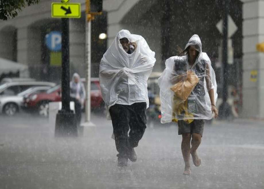 Delegates run for shelter in a downpour as they arrive at the Democratic National Convention in Charlotte, N.C., on Thursday, Sept. 6, 2012.  (David Goldman / Associated Press)