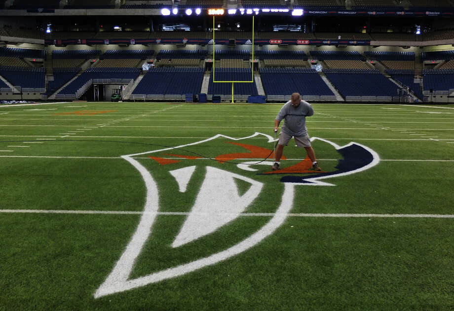 Alamodome facility operations coordinator Tom McAfee applies some blue while painting UTSA's logo on the field Thursday. Photo: Kin Man Hui, SAN ANTONIO EXPRESS-NEWS / ©2012 San Antonio Express-News
