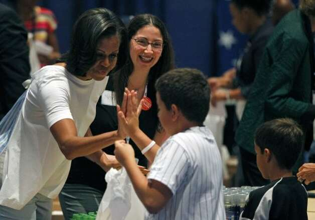 First lady Michelle Obama gives a high five to Jonathan Ruiz as they help fill bags for a USO service project during the Democratic National Convention in Charlotte, N.C., Thursday, Sept. 6, 2012.  (Chuck Burton / Associated Press)