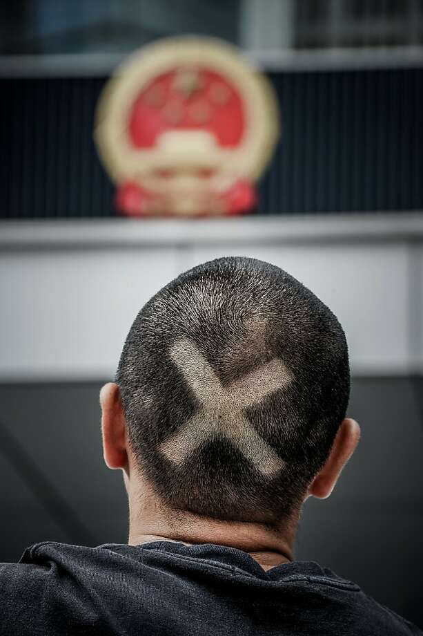A student with a symbol shaved on his head joins protesters at government offices in Hong Kong. Photo: Philippe Lopez, AFP/Getty Images