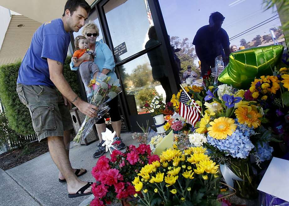A man who declined to give his name and Fran Meyers add flowers to the memorial that continues to grow outside the Martinez office of the California Highway Patrol. Flags in the state are flying at half-staff. Photo: Brant Ward, The Chronicle