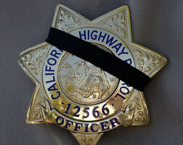 Officers wear black tape on their badges in memory of their fallen colleague. Photo: Brant Ward, The Chronicle
