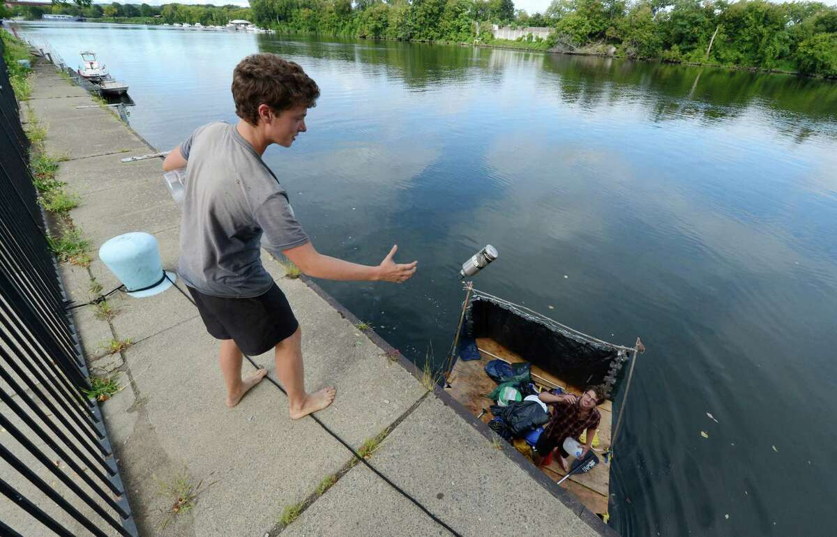 On the adventure of a lifetime are Robin King, 19 of Nyack, foreground and Peter Herse 21 of Port Washington stopped their homemade raft in Troy, N.Y. Sept. 5, 2012 to pickup some water. (Skip Dickstein/Times Union)
