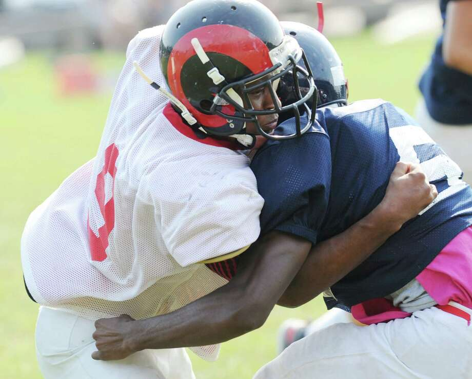 At left, Mykal Morris # 9 of Bridgeport Central High School, tackles running back Trevon Forney # 5 of Brien McMahon during the high School football jamboree at Wilton High School, Saturday morning, Sept. 1, 2012. Photo: Bob Luckey / Greenwich Time