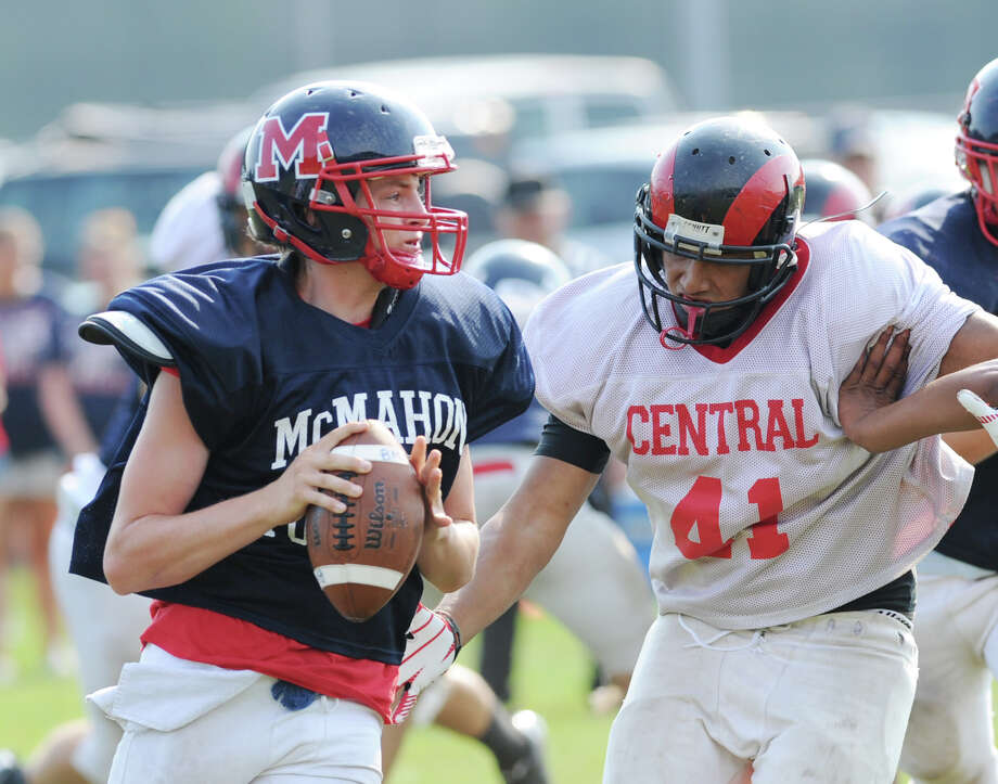 At right, Bridgeport Central High School's Erick Cuatzo, # 41, pressures Brien McMahon quarterback Trey Newcomb, left, in a scrimmage during the high School football jamboree at Wilton High School, Saturday morning, Sept. 1, 2012. Photo: Bob Luckey / Greenwich Time