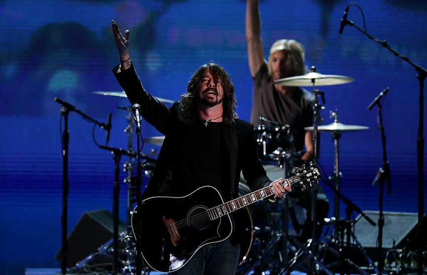 Dave Grohl, left, and Taylor Hawkins of the Foo Fighters gesture after performing on day three of the Democratic National Convention (DNC) in Charlotte, North Carolina, U.S., on Thursday, Sept. 6, 2012. President Barack Obama's prime-time nomination acceptance speech tonight at the DNC will be aimed at convincing voters that a slow economic recovery will accelerate if they give him a second term.