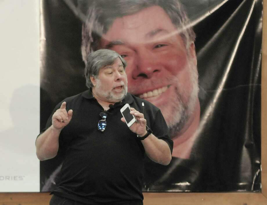 Steve Wozniak, co-founder of Apple computers, holds up his iPhone as he gives a talk to students, faculty, staff and guests 