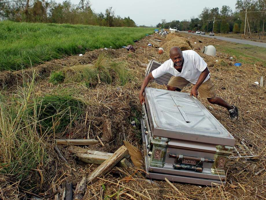 Dwight Robinson, 59, looks for the casket of his mother, Irma LeBlanc Robinson, on the Mississippi River levee, Wednesday, Sept. 5, 2012.  She died in 1995 at the age of 81 and was buried in the Bertrandville Cemetery in Plaquemines Parish. Hurricane Isaac and its 15 of storm surge decimated that cemetery and floated caskets and crypts at least a quarter mile. Photo: David Grunfeld, Associated Press / The Times-Picayune