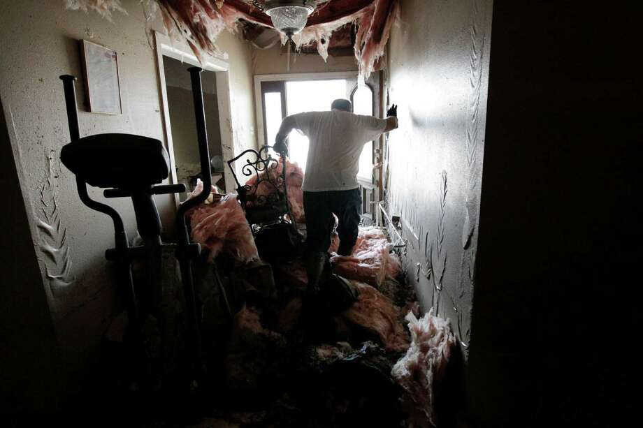 Insulation hangs from ceilings as Darryl Dragon walks through his daughters bedroom in his flooded home after floodwaters from Hurricane Isaac receded in Braithwaite, La., Thursday, Sept. 6, 2012. Photo: Gerald Herbert, Associated Press / AP