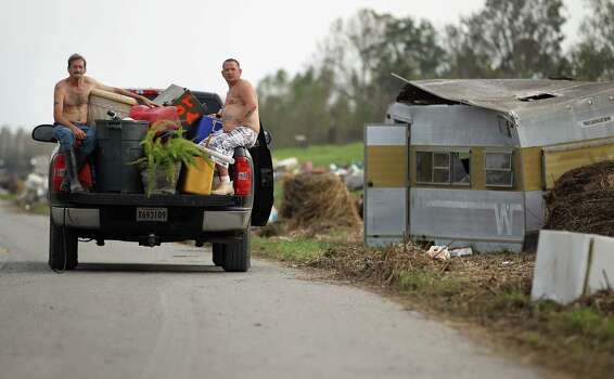 Men ride in a pickup truck while savaging items washed up onto a  levee in Paquemines Parish on September 5, 2012 in Braithwaite, Louisiana.  Louisiana officials estimate that at least 13,000 homes were damaged by Hurricane Isaac. Photo: Mario Tama, Getty Images / 2012 Getty Images