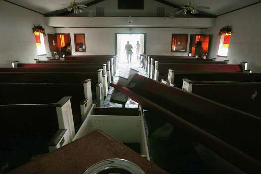An insurance inspector tours the damaged Bethehem Baptist Church which flooded in Plaquemines Parish on September 5, 2012 in Braithwaite, Louisiana. Louisiana officials estimate that at least 13,000 homes were damaged by Hurricane Isaac. Photo: Mario Tama, Getty Images / 2012 Getty Images