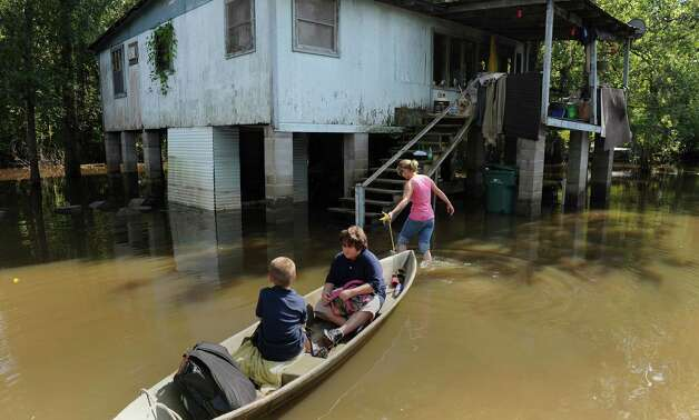 Samantha Jean uses a small boat to ferry her two sons, Caleb, 6, left, and Zane, 10, to their home through flood waters, Thursday, Sept. 6, 2012 off La 22 near Head of Island La.  Jean said until the flood water brought by Hurricane Isaac leaves her yard she will bring the boys home in the boat to keep them clean and safe. Resident in Livingston Parish continue to deal with flood waters surrounding homes and covering some streets more then a week after Hurricane Isaac moved through the area. Photo: Arthur D. Lauck, Associated Press / The Advocate