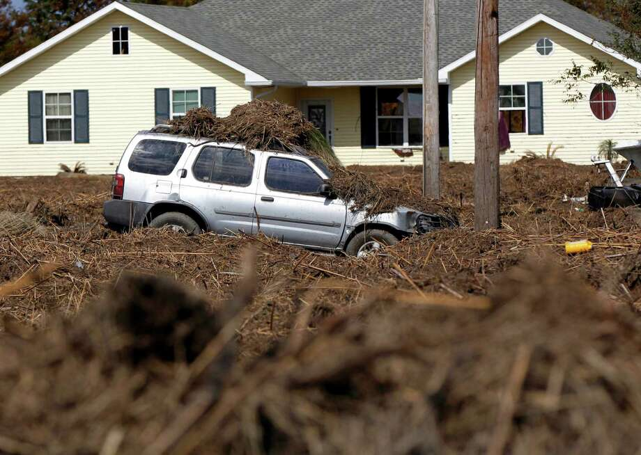 A car and lawn are covered in marsh grass after floodwaters from Hurricane Isaac receded in Braithwaite, La., Thursday, Sept. 6, 2012.  Isaac hit southeast Louisiana and coastal Mississippi last week, causing severe flooding and seven deaths. Photo: Gerald Herbert, Associated Press / AP