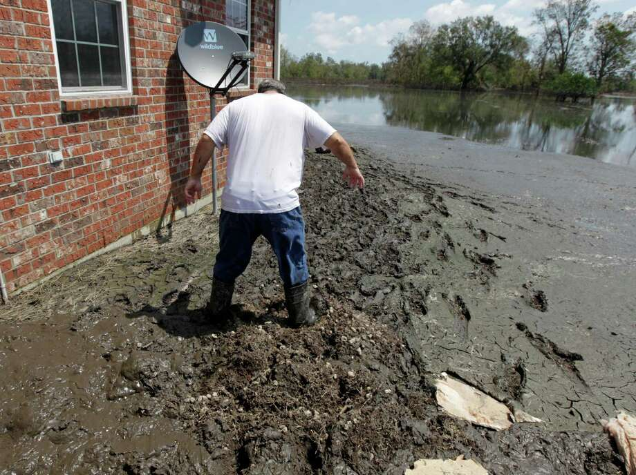 Darryl Dragon walks through through thick , smelly mud outside his home after floodwaters from Hurricane Isaac receded in Braithwaite, La., Thursday, Sept. 6, 2012. Water rose into the attic during the storm. Photo: Gerald Herbert, Associated Press / AP