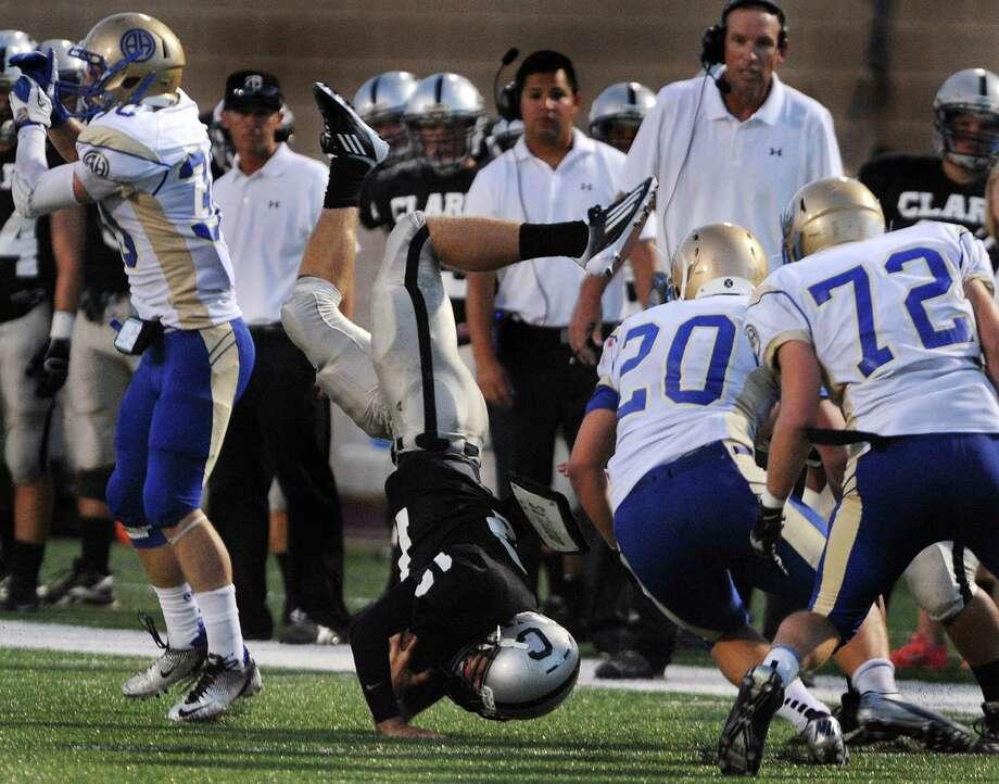 Clark quarterback Chase Jones goes head over heels after taking a hit Thursday night at Farris Stadium. Photo: Billy Calzada, San Antonio Express-News / © San Antonio Express-News
