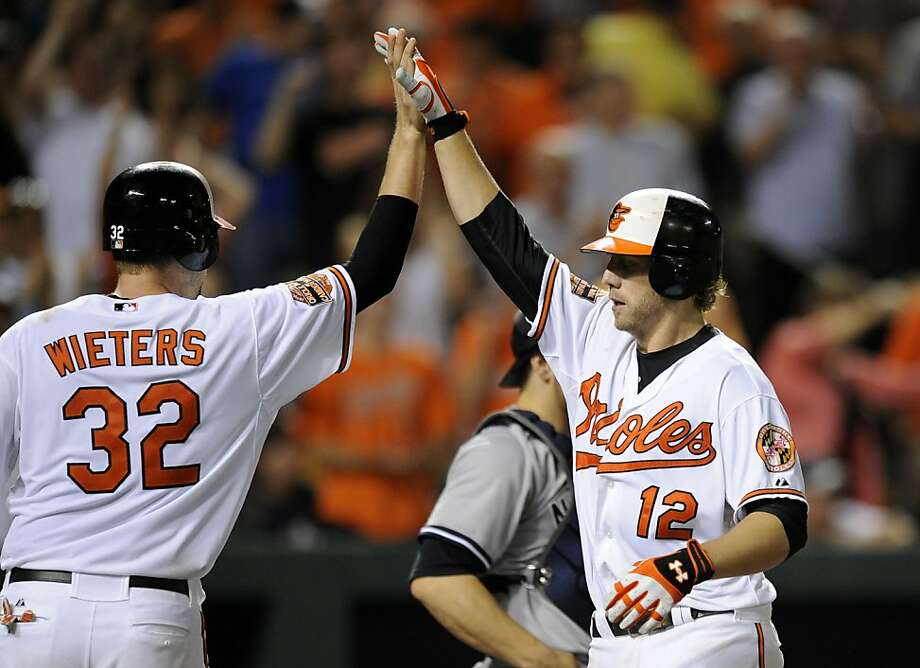 Baltimore Orioles' Mark Reynolds (12) celebrates his two-run home run with Matt Wieters against the New York Yankees during the eighth inning. Photo: Nick Wass, Associated Press