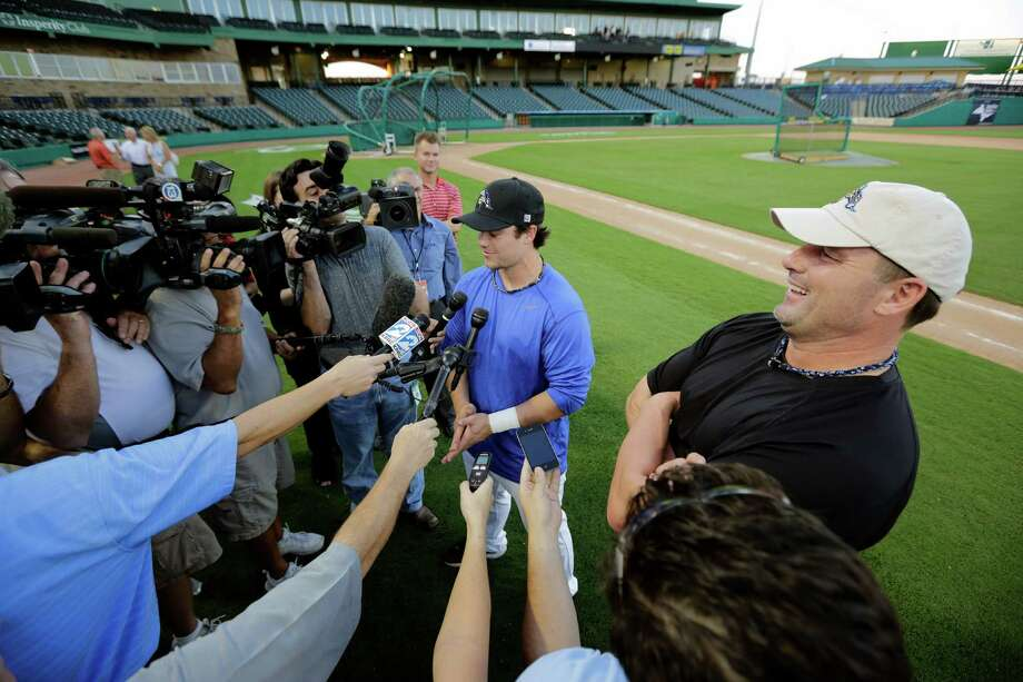 Roger Clemens appears to be having all the fun as he watches son and batterymate Koby Clemens handle the media during Thursday's workout at Constellation Field in Sugar Land. The younger Clemens will catch his father tonight. Photo: TODD SPOTH / Todd Spoth