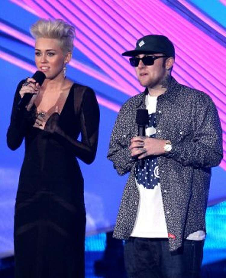 Miley Cyrus (with co-presenter Mac Miller) channels Pink with her new haircut as she presents the pop star's performance. (Matt Sayles / Associated Press)