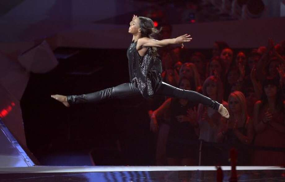 Olympic gymnast Gabrielle Douglas leaps onstage (in leather pants) at the MTV Video Music Awards on Thursday, Sept. 6, 2012, in Los Angeles.  (Mark J. Terrill / Associated Press)