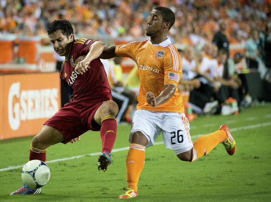Real Salt Lake defender Tony Beltran, left, fights to control the ball against Houston Dynamo midfielder Corey Ashe during an MLS soccer match on Thursday, Sept. 6, 2012, at BBVA Compass Stadium in Houston. Photo: Smiley N. Pool, Houston Chronicle / © 2012  Houston Chronicle