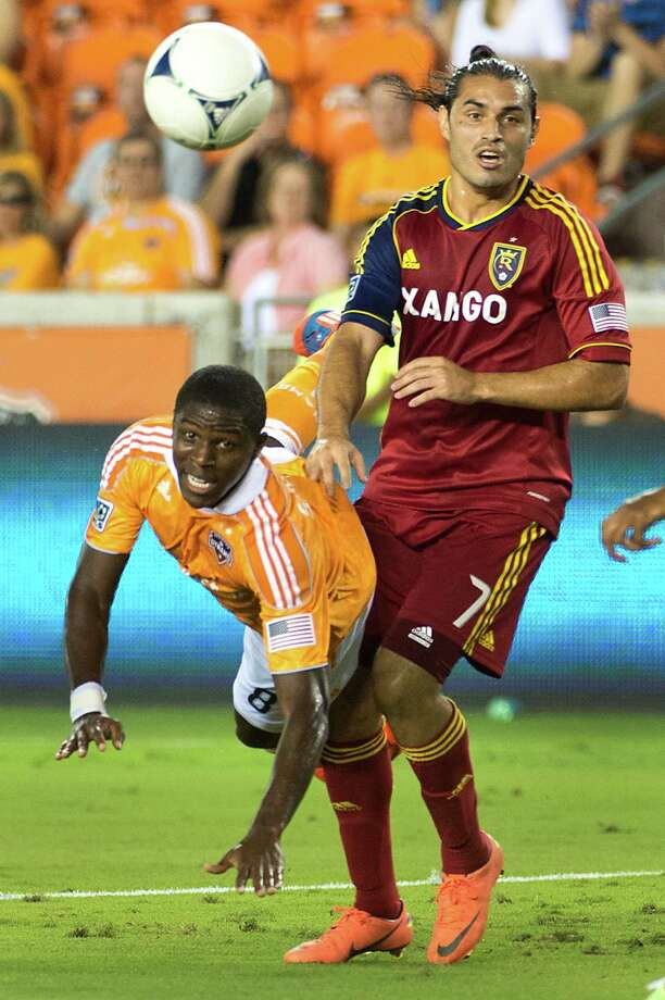 Houston Dynamo defender Kofi Sarkodie (8) dives for a ball against Real Salt Lake forward Fabian Espindola (7) during an MLS soccer match on Thursday, Sept. 6, 2012, at BBVA Compass Stadium in Houston. Photo: Smiley N. Pool, Houston Chronicle / © 2012  Houston Chronicle
