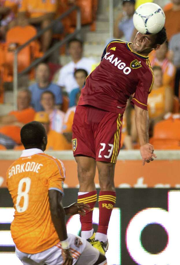 Real Salt Lake forward Paulo Jr. (23) heads the ball over Houston Dynamo defender Kofi Sarkodie (8) during an MLS soccer match on Thursday, Sept. 6, 2012, at BBVA Compass Stadium in Houston. Photo: Smiley N. Pool, Houston Chronicle / © 2012  Houston Chronicle