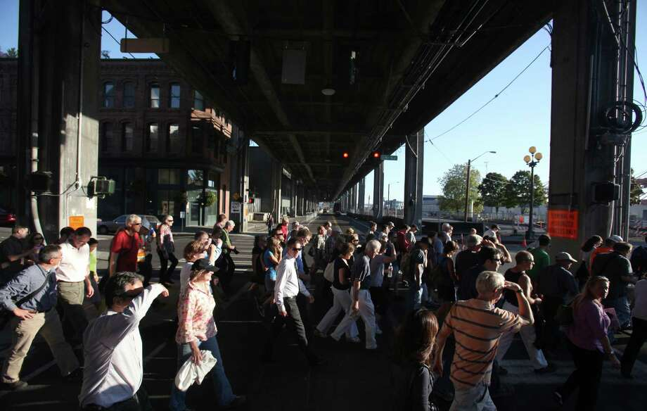 People cross under the Viaduct during a tour of the Highway 99 tunnel site along the Alaskan Way Viaduct as crews prepare for the arrival of the world's largest-diameter tunnel boring machine which will dig under downtown Seattle. The public was offered a tour of the site on Thursday, September 6, 2012. Photo: JOSHUA TRUJILLO / SEATTLEPI.COM