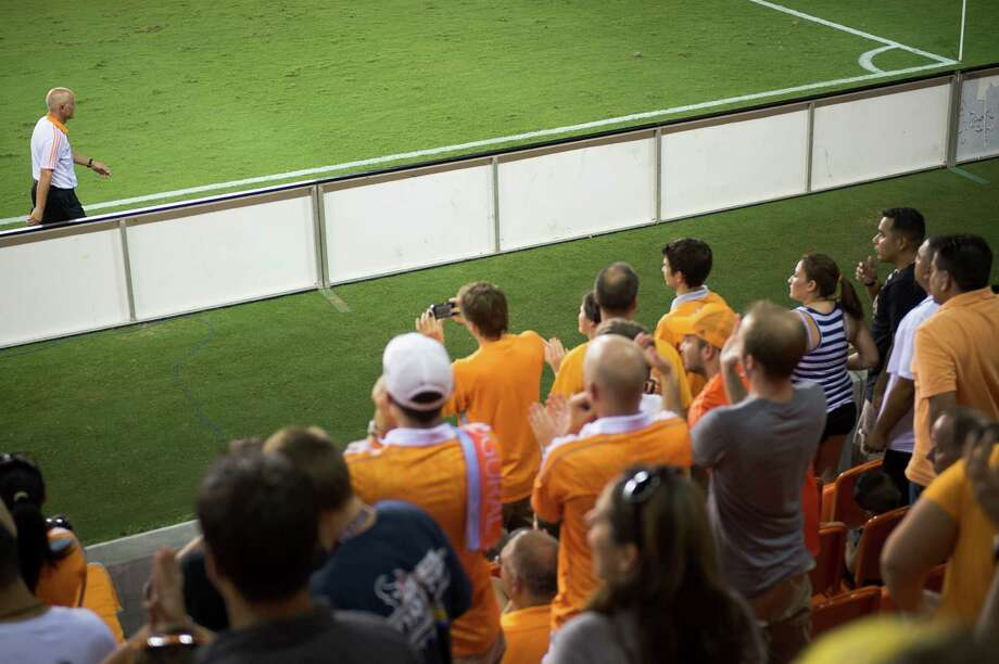 Houston Dynamo head coach Dominic Kinnear gets a hand from the home crowd as he leaves the pitch after being ejected during the second half of an MLS soccer match against Real Salt Lake on Thursday, Sept. 6, 2012, at BBVA Compass Stadium in Houston. Photo: Smiley N. Pool, Houston Chronicle / © 2012  Houston Chronicle