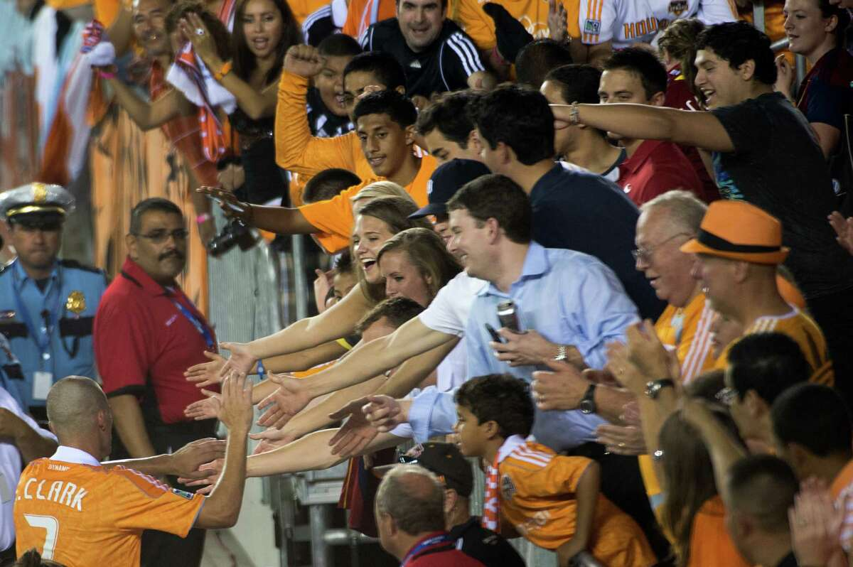 Houston Dynamo midfielder Colin Clark celebrates with fans after a 1-0 victory over Real Salt Lake in an MLS soccer match on Thursday, Sept. 6, 2012, at BBVA Compass Stadium in Houston. Clark converted a penalty kick in stoppage time for the victory.