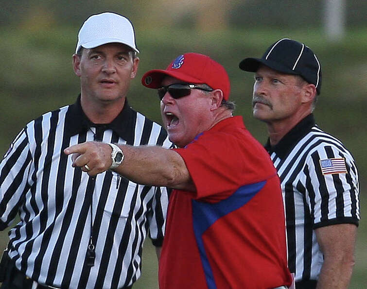 Dulles head coach Jim Creech argues with officials during the first half of a high school football g