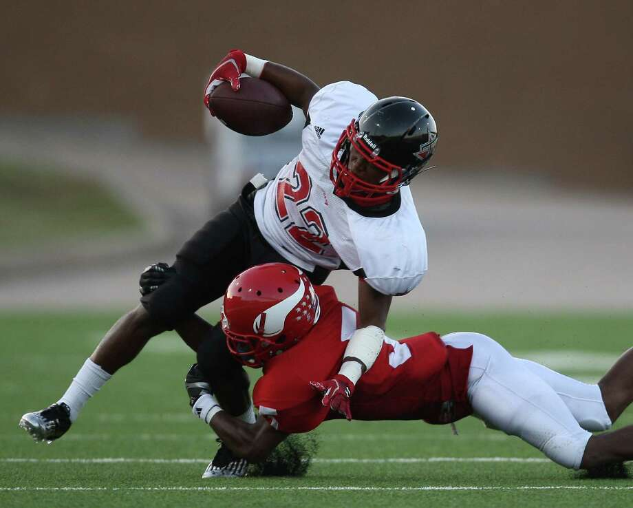 Terry's Eugene Wright (22) is tackled by Dulles' Jermaine Walker during the first half of a high school football game, Thursday, September 6, 2012 at Mercer Stadium in Sugar Land, TX. Photo: Eric Christian Smith, For The Chronicle