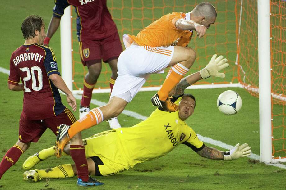 Despite onrushing Dynamo forward Will Bruin, center, Real Salt Lake goalkeeper Nick Rimando, right, keeps the ball out of the net. Rimando was successful for 90 minutes, but the Dynamo's Colin Clark netted a penalty kick in stoppage time for the win. Photo: Smiley N. Pool / © 2012  Houston Chronicle