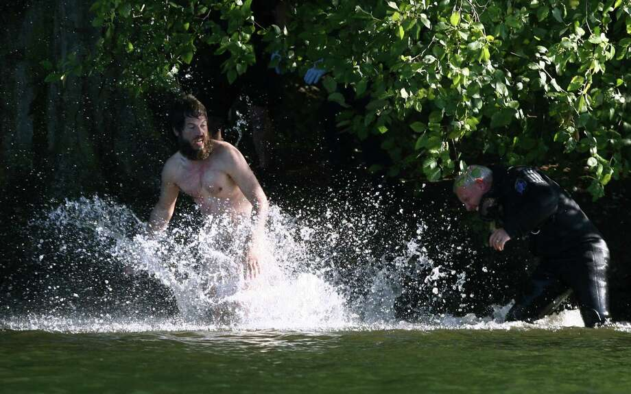 Officers pursue as a naked man runs from Seattle police officers after police said he assaulted two children at Green Lake Park and was chased into the middle of Green Lake. He clung naked to a buoy before swimming to Duck Island where he continued to evade police for about 2 hours. They finally arrested the man. The chase was covered live by television helicopters and followed closely on social media. Photo: JOSHUA TRUJILLO / SEATTLEPI.COM