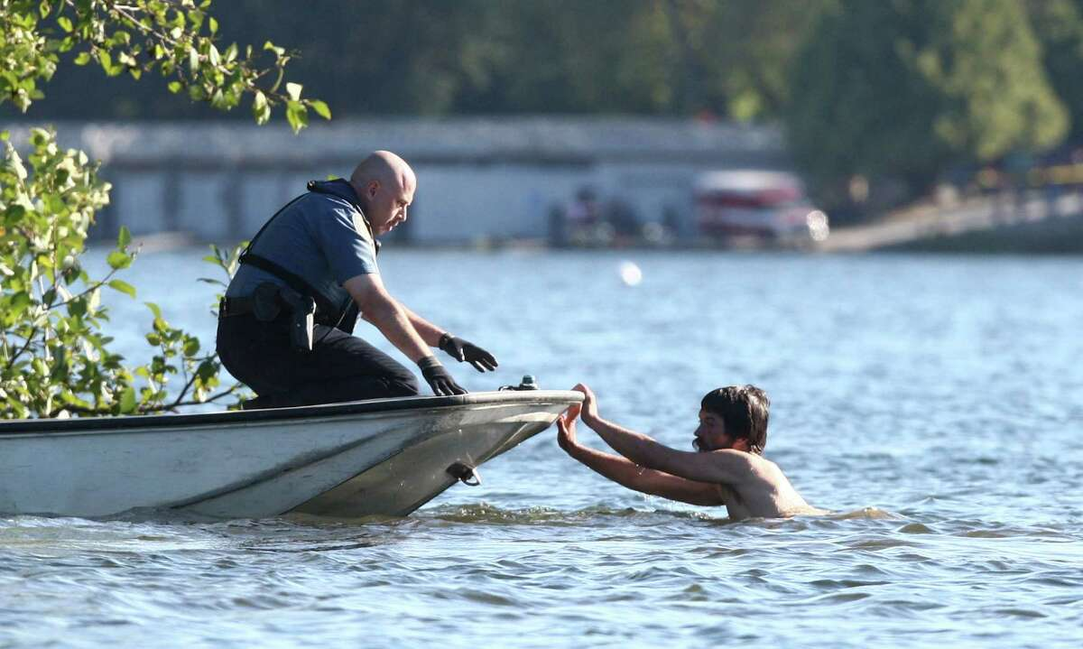A naked man pushes on a boat with a Seattle police officer aboard as officer pursue the man.